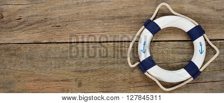 White lifebuoy on a wooden background close up