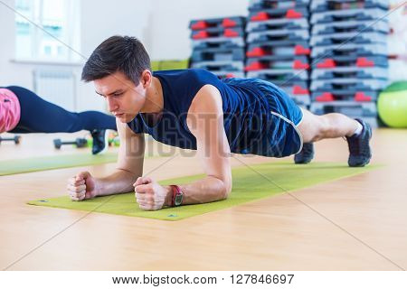Fitness training athletic sporty man doing plank exercise in gym or yoga class exercising workout.
