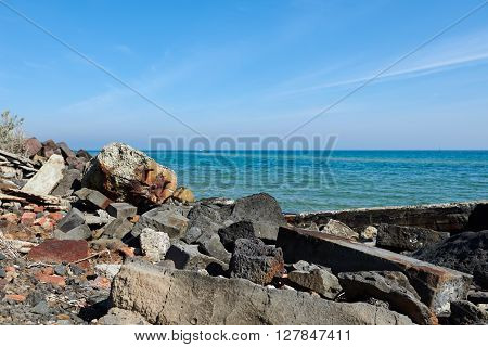 Litter on the beach against a blurred background of pristine blue  ocean and sky