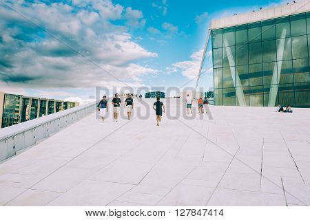 OSLO, NORWAY - JULY 31, 2014: People walking on the roof of The Oslo Opera House Is The Home Of The Norwegian National Opera And Ballet
