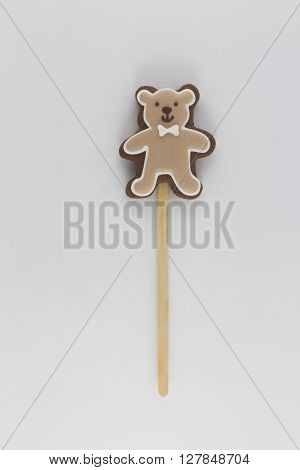 Cookies in the form of a brown bear on wooden sticks . brown teddy bear with a white butterfly .