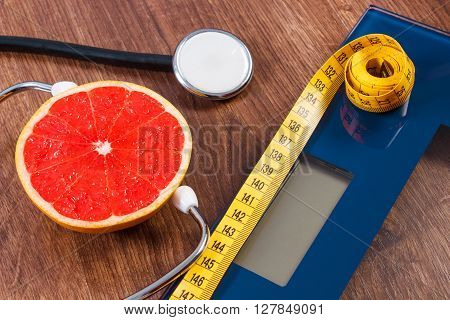 Digital electronic bathroom scale for weight of human body tape measure and medical stethoscope with fresh grapefruit concept of healthcare healthy lifestyles and slimming