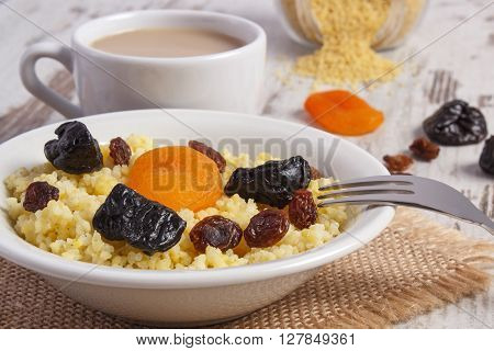 Cooked millet groats with raisins dried apricot and plum on white plate cup of coffee with milk concept of healthy food nutrition and nutritious breakfast