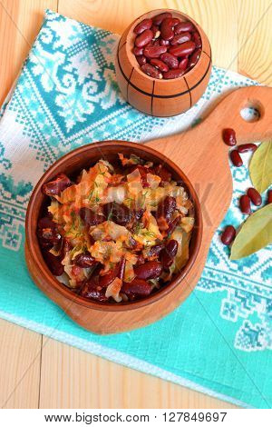 Stewed cabbage with red beans, a small barrel of raw beans, spices on the wooden background in rustic style