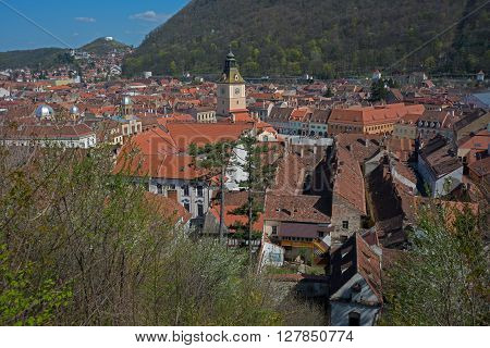 Many red tale roofs are surrounded Brasov state house tower. Brasov is famous Transylvania (Romania) town.