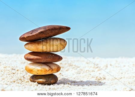Five white and brown stones are on sandy beach