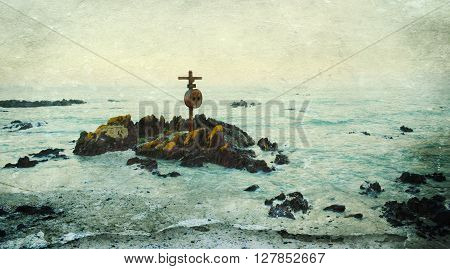 Seascape with rocky coast and Cross at sunrise