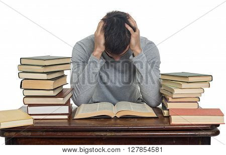 Tired young man reading book at table isolated on white