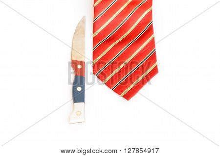 Closeup of knife and red tie on white background.