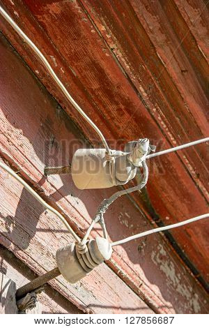 Two Old Ceramic insulators on the wooden wall of slum house. Connection wiring.