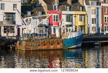 Weymouth, UK - April, 17, 2016. Fishing boat moored by colourful shops in Weymouth Harbour Dorset. Weymouth is a fishing harbour and tourist resort.