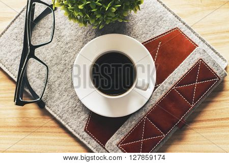 Topview of grey and brown tablet case with coffee cup glasses and plant on wooden desktop