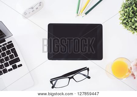 Topview of blank tablet on white desktop with notebook glasses plant clock pencils and hand holding glass with orange juice. Mock up