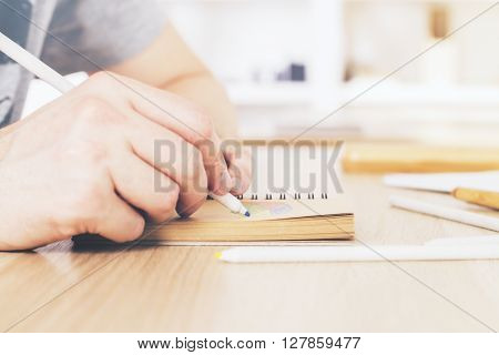 Sideview of male hand drawing in aged notepad with blurry office in the background