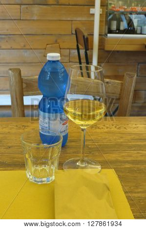 ROME ITALY - CIRCA OCTOBER 2015: a wooden table with a yellow paper placemat a gass of wine an empty glass and a bottle of water