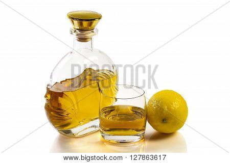 Bottle and a glass of whiskey with a lemon on a white background