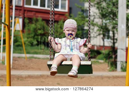 Cute little girl in hat with pacifier riding on swing on summer sunny day