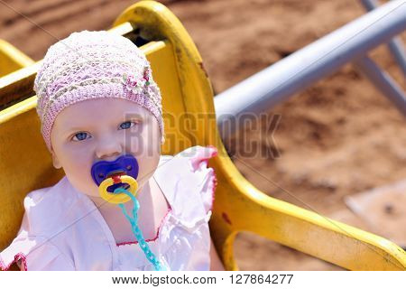 Cute little girl in hat with pacifier riding on carousel on summer sunny day