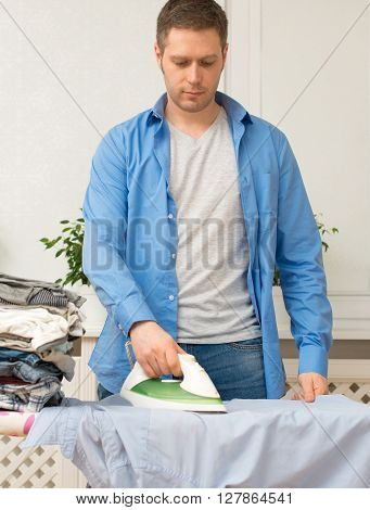 Handsome Man Ironing Clothes On Ironing Board At Home.