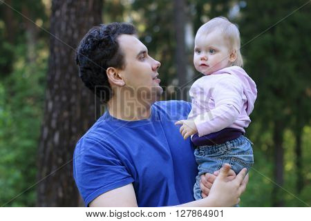 Young handsome man holds his little cute daughter in summer park