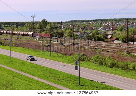 Freight train with tanks stand on railway station and car moves on asphalt road