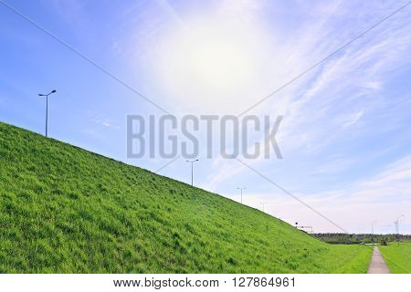 Sun in blue sky bright green lawn walkway and road on hill at summer