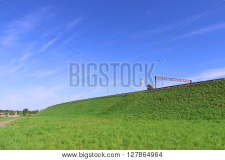 Pure blue sky bright green lawn and road on hill at summer sunny day