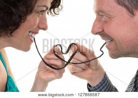 Couple Eating Licorice Forming A Heart With It, Passion