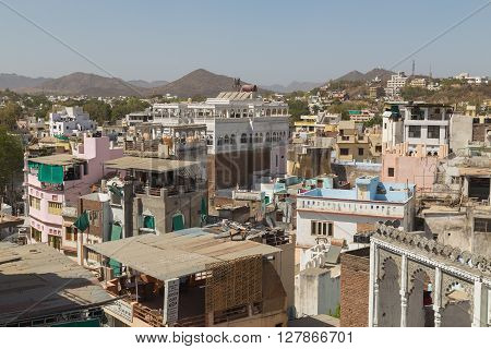 UDAIPUR INDIA - 20TH MARCH 2016: A high view over rooftops in Udaipur during the day. The outside of buildings and hills can be seen.