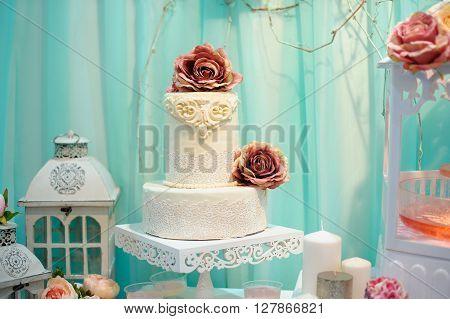 White wedding cake decorated sugar pattern on table.