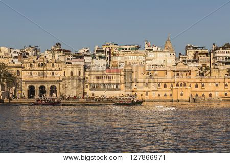 UDAIPUR INDIA - 20TH MARCH 2016: A view of part of the City of Udaipur at the lake waterfront during the day close to sunset. People and boats can be seen.