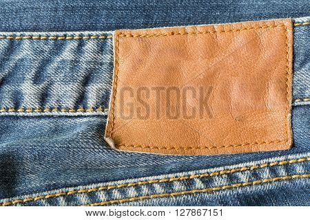 brown leather tag on blue jeans, clothing design