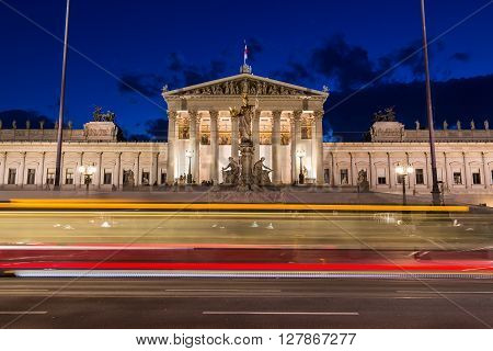 The outside of the Austrian Parliament building in Viennat at night. The blur of a tram can be seen going past in the foreground.