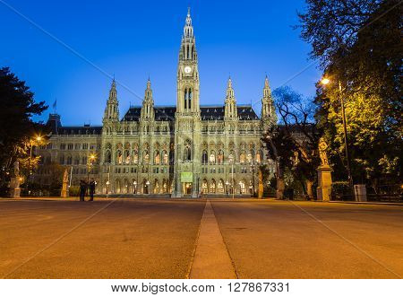 VIENNA AUSTRIA - 22ND APRIL 2016: The outside of the Rathaus (Vienna City Hall) at night front the front. People can be seen.
