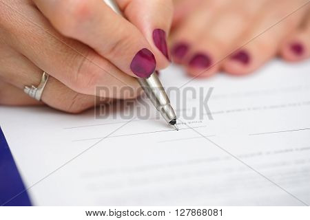 close up of female hand signing document