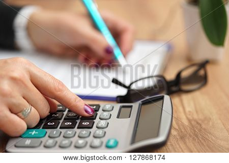 Business woman using calculator for fulfilling document for her business