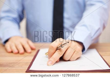 Businessman is showing client where to sign very good deal or employment contract