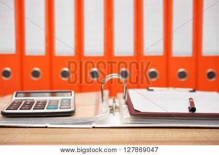 calculator and document on top of open folder with documentation in background accounting concept