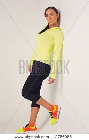Beautiful sporty fit young woman in green and black sportwear over white background.