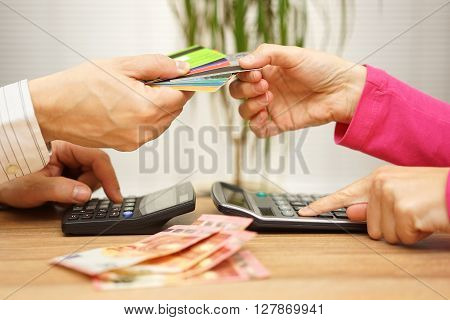 man and woman are calculating how will they spend their tight salaries and which credit card they will use