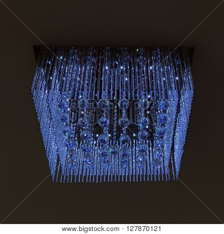 Chandelier Crystal Blue Light On Black Wall Background
