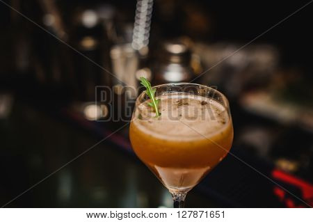 Wine glass with cocktail on bar background with rocket