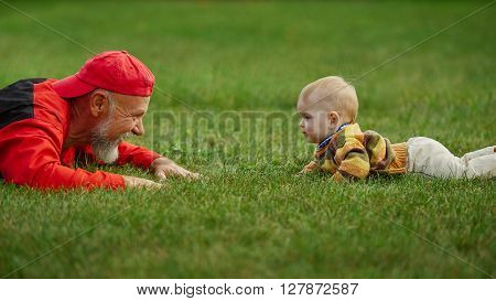 happy grandfather and grandson lying on grass