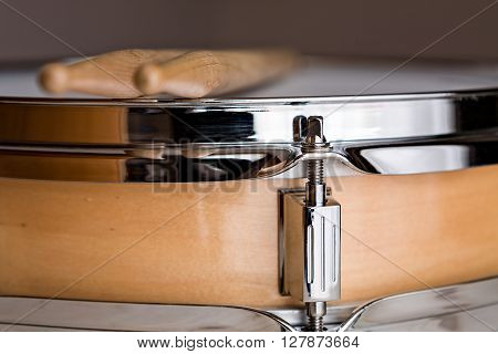 Close up of a wooden snare drum with drumsticks above