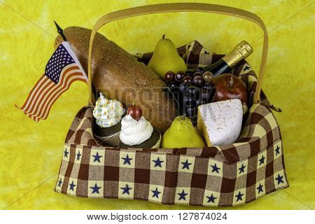 picnic basket of fruits cheese bread wine cupcakes and American flag on yellow background