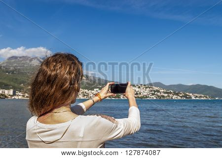 A young woman stands on the shore of the bay in Montenegro and does selfie