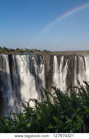 Victoria Falls in October with rainbow crossing. Waterfall running at low speed. Water slightly blurred.
