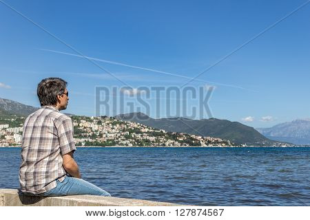 The man on the Montenegrin coast bay looking at the horizon