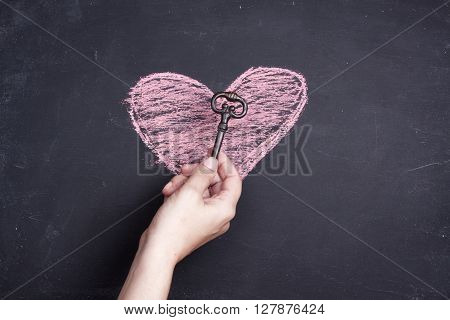chalk heart drawing and key on a black background