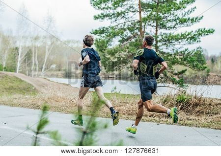 two leading athletes runners running down road in Park past lake